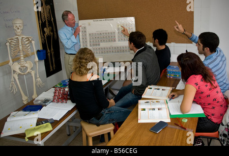 Teacher and senior teenage school students in science classroom studying elements table in organic chemistry - Stock Photo
