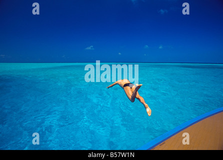 Man jumping into tropical sea from deck, Maldives, Indian Ocean, Asia - Stock Photo