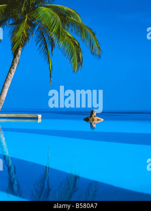 Woman in swimming pool under palm tree looking at sea, Maldives, Indian Ocean, Asia - Stock Photo