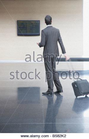 Businessman checking flight times - Stock Photo