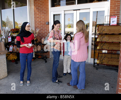 Teenage girls giving away free energy efficient light bulbs to people for an environmental community service project - Stock Photo