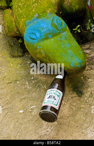 Belize City green stone alligator blue eyes bottle local Belikin beer in mouth humor humour odd funny - Stock Photo