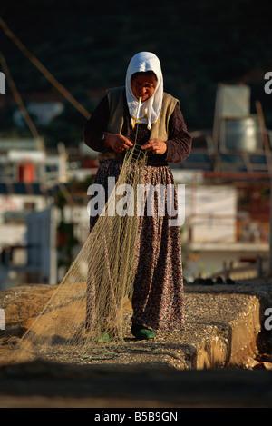 Woman in traditional baggy trousers mending a fishing net, Kas, Anatolia, Turkey Minor, Eurasia - Stock Photo