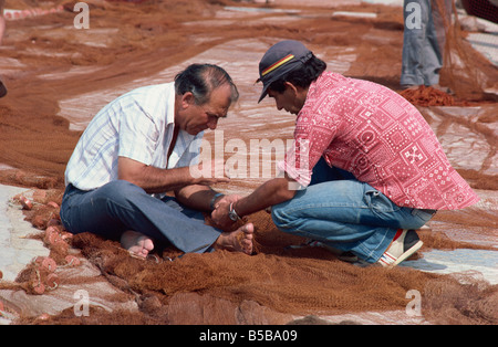 Fishermen mending nets on quayside, Nazare, Portugal, Europe - Stock Photo