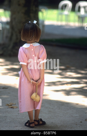 Little girl in a pretty red checked dress and bow in her hair in a park - Stock Photo