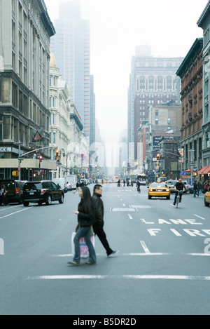 Pedestrians crossing street in crosswalk at W 19th Street and 6th Avenue Chelsea, New York, facing NE - Stock Photo