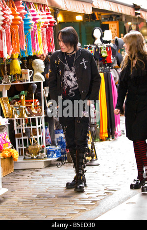 Camden Stables Market teenage male boy in Gothic leather gear with buckled boots long hair & mascara walks with - Stock Photo