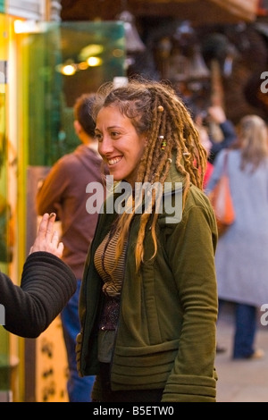 London Camden Stables Market pretty female girl or lady or adult smiling teenage girl with blond dreadlocks chats - Stock Photo