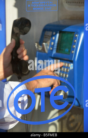 Man dialing a telephone number at a public phone booth in Rhodes, Greece - Stock Photo