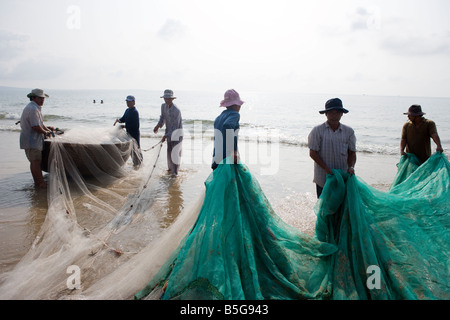 Fishermen on the beach at Mui Ne. Woven coracles are traditional boats used in the area. Vietnam - Stock Photo
