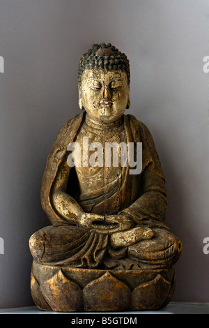 A wooden statue of Buddha sitting in the Lotus position isolated on gray - Stock Photo