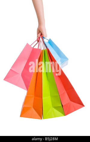 Woman hand holding several shopping paper bags isolated on white. female carrying bag cut out cutout spree grabbing - Stock Photo