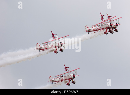 Win walkers from Team Guinot wing walking Areobatic Display team are pictured standing on their Boeing Stearman - Stock Photo