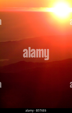 powerful dramatic sunset sunrise in mountains red orange yellow sun sunbeams over the clouds landscape sky dream - Stock Photo