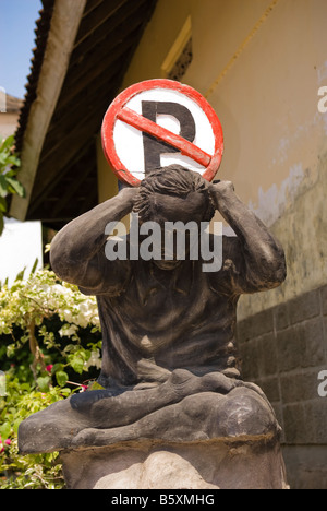 No parking sign on top of a sculpture or statue of a man appearing to have the burdens of the world upon him - Stock Photo