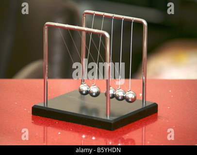 Newton's Cradle game on red table - Stock Photo