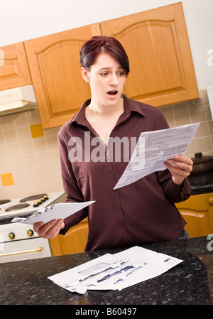 Young woman opens a letter at home and looks in shock at the size of the bill enclosed MR PR - Stock Photo
