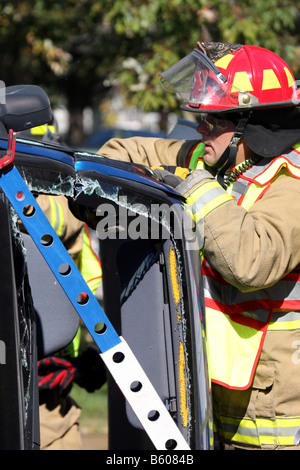 firefighter has used the jaws of life extrication tool to cut through a support column of a car that has rolled - Stock Photo