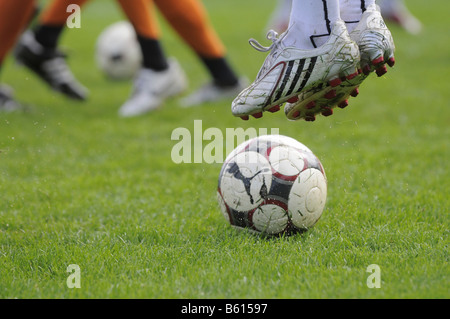 Soccer ball and boots and legs of soccer players, Kirchheim/Teck, Baden-Wuerttemberg - Stock Photo