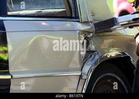 Firefighters using an extrication tool to gain entry in a vehicle - Stock Photo