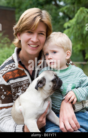Young woman, 30+, child, boy, 2, dog, pug, puppy, portrait - Stock Photo