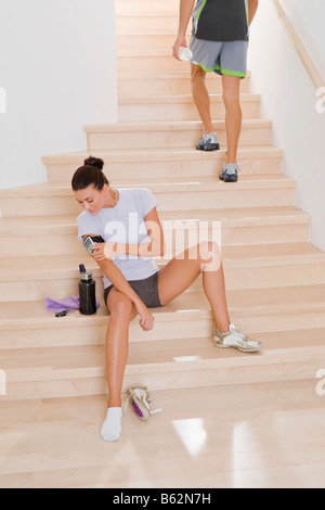Young woman looking at a pedometer on her arm - Stock Photo
