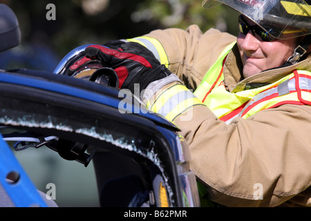 A firefighter has used the jaws of life extrication tool to cut through a support column of a car that has rolled - Stock Photo