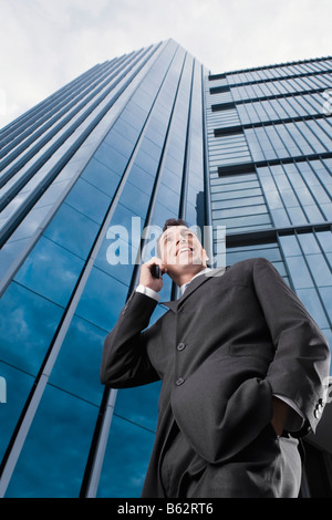 Low angle view of a businessman talking on a mobile phone and smiling - Stock Photo