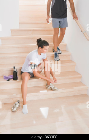 Young woman sitting on a staircase and tying her shoelace - Stock Photo