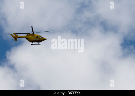 A yellow air ambulance helicopter against a cloudy but blue sky - Stock Photo