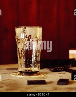 a color colour picture of a drained glass of beer, lager, stout or guiness in a bar - Stock Photo