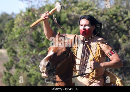 An Apache Native American Indian running horseback waving a stone hammer in attack - Stock Photo