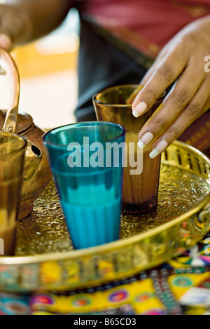 Milk tea being prepared in colored glasses on tea tray - Stock Photo