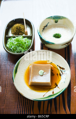 Sesame tofu with wasabi, green tofu noodles with spices and savory soy cream with shiso garnish - Stock Photo