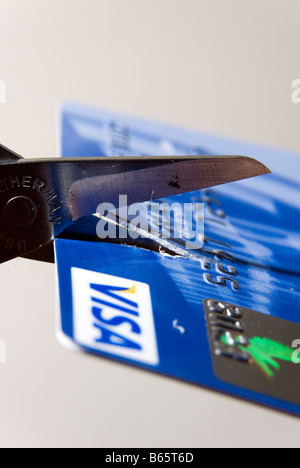 Scissors cutting up bank credit card - Stock Photo