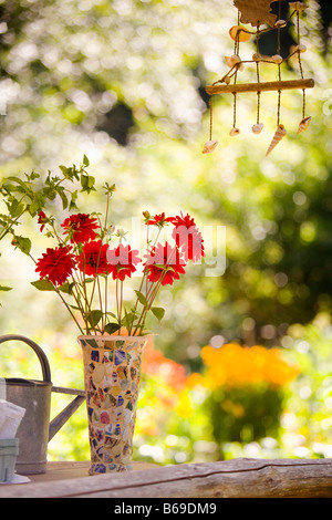 Watering can with a vase of flowers and a wind chime - Stock Photo