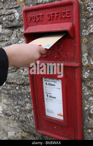Posting a letter in an Royal mail post box. - Stock Photo