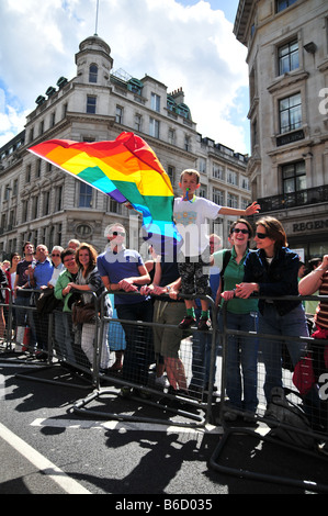 A young boy waves the Gay Pride Rainbow flag - Stock Photo