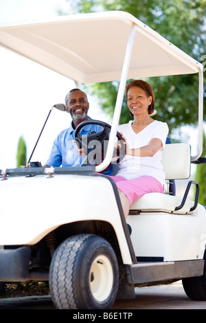 Golf players. Husband and wife using a golf cart during a round of golf. - Stock Photo
