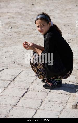 Turkman girl praying at the shrine of Jamal al-Din, Anau, Turkmenistan - Stock Photo