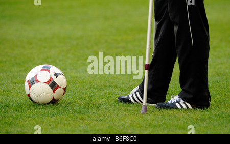Injured football player on crutches, partial view, on grass with a football - Stock Photo