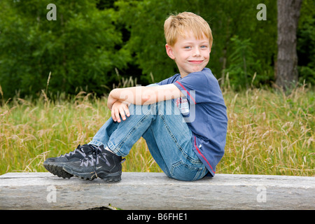 A boy, six years old, sitting on a wooden bench in front of a deciduous forest - Stock Photo
