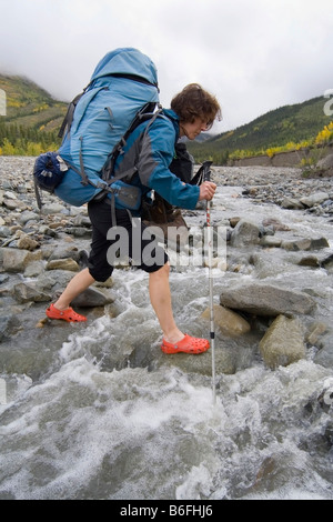 Young woman, backpacker, hiker wading through a creek, St. Elias Mountains, Donjek Route, Kluane National Park, - Stock Photo