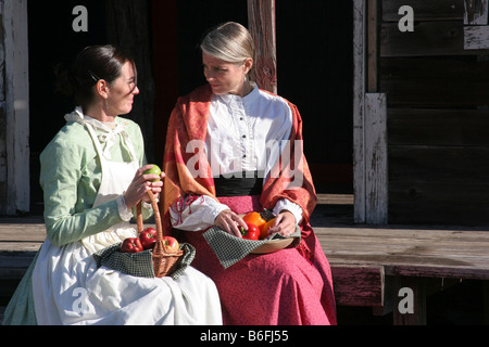 Two young prairie women sitting with fresh picked fruits and vegetables - Stock Photo