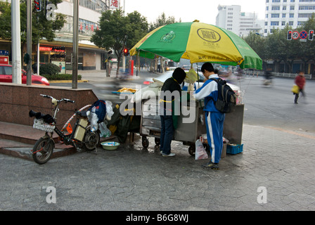 School boy buying breakfast from roadside food vendor stall on downtown street corner with busy traffic in motion - Stock Photo
