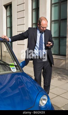 Man sending message on mobile phone - Stock Photo