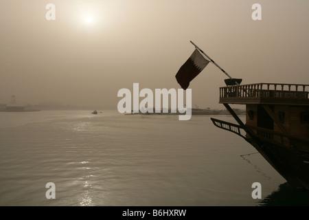 Qatari flag on traditional boat in sunlit haze, Doha Bay,Doha, Qatar, Middle East - Stock Photo
