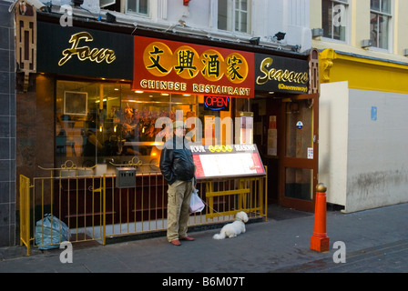 Man and a dog in front of a restaurant in Gerrard Street in Chinatown in central London England UK - Stock Photo