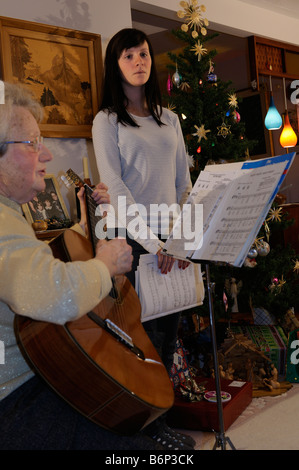 Grandmother playing guitar and teenage granddaughter singing Christmas carols indoors at home by the decorated tree - Stock Photo