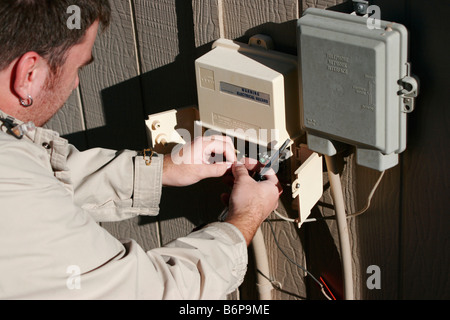 A telephone repairman makes an adjustment on a wiring connection while repairing the phone line - Stock Photo